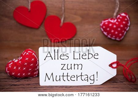 Label With German Text Alles Liebe Zum Muttertag Means Happy Mothers Day. White Label With Red Textile Hearts. Retro Brown Wooden Background.