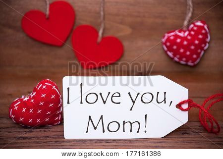 Label With English Text I Love You Mom. White Label With Red Textile Hearts. Retro Brown Wooden Background.