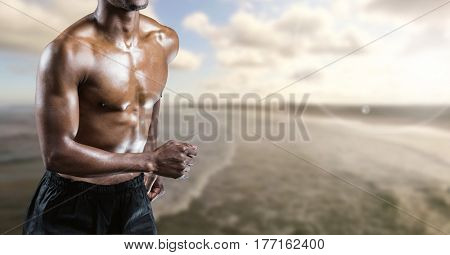 Digital composite of Fitness man torso who is running along the sea