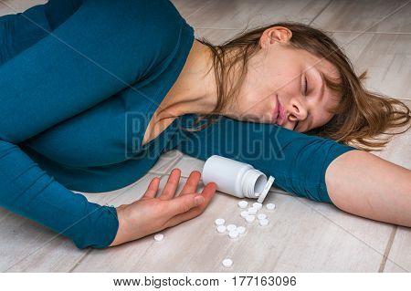 Woman committing suicide with pills - depression woman lying on the floor at home after an overdose of pills poster