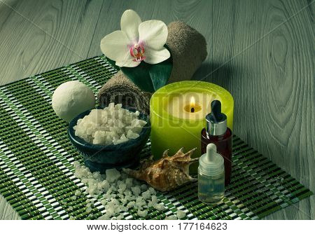 Spa and wellness setting with orchid flower bowl with sea salt seashell bottles with aromatic oil candle and towel on bamboo napkin
