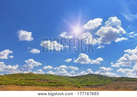 sun shining on the blue sky with clouds