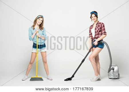 Two beautiful young women standing with broom and vacuum cleaner smiling at camera