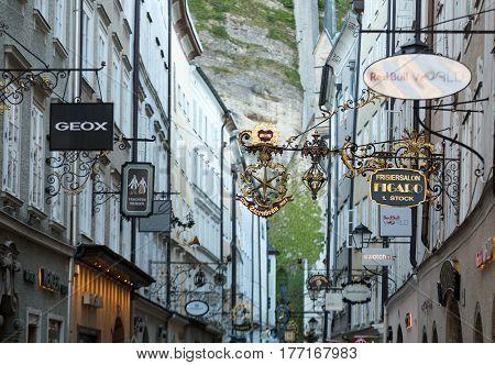 SALZBURG AUSTRIA - APRIL 29 2016: Shopping street in Salzburg -Getreidegasse with multiple advertising signs. Getreidegasse is one of the oldest streets in Salzburg
