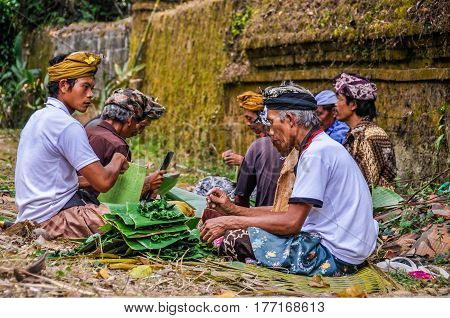 BALI, INDONESIA - SEPTEMBER 27, 2012: Balinese people preparing the offerings in the Tirta Empul Temple in Bali Indonesia