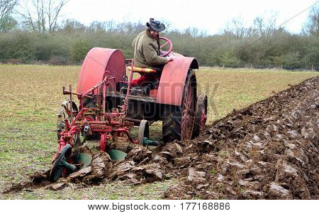 ST NEOTS, CAMBRIDGESHIRE, ENGLAND - MARCH 19, 2017: Vintage red International 1930's  tractor ploughing field.