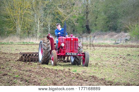 ST NEOTS, CAMBRIDGESHIRE, ENGLAND - MARCH 19, 2017: Vintage red International 1960's  tractor ploughing field.