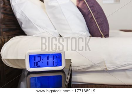 Alarm clock electronic stands on a bedside table near the bed