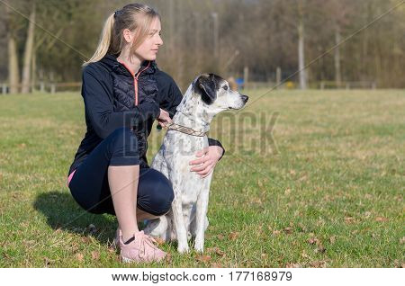 Pretty young woman teaching her dog commands kneeling down in a field alongside it looking to the side as the animal looks alertly in that direction