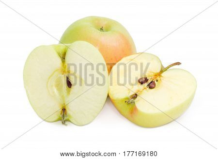 One whole and one cut in half with seeds of the green-pink apple on a light background