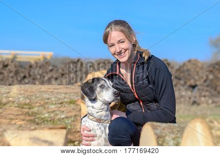 Happy Loving Young Woman Cuddling Her Dog
