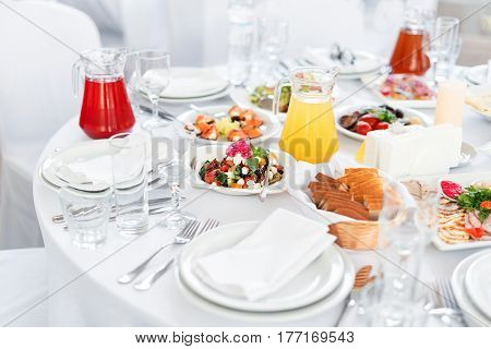 Restaurant table with food. Tasty appetizers, salads. Different meals for the guests on the wedding table.