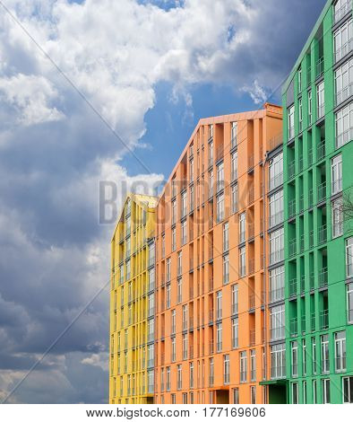 Fragment of a multicolored facade of the modern multi-story apartment complex against the background of the sky with storm clouds