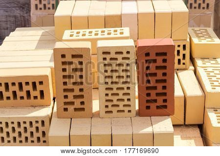 Three perforated bricks of white yellow and red colors with rectangular holes on a pallet with bricks on the background other bricks on a warehouse