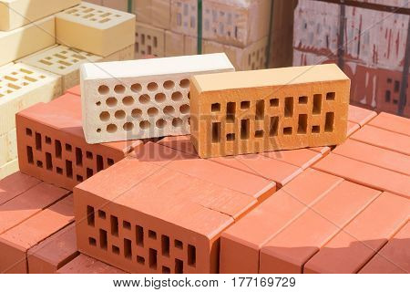 White brick with a round holes and yellow brick with a rectangular holes from above on a pallet with the red perforated bricks on the background of other bricks on a warehouse