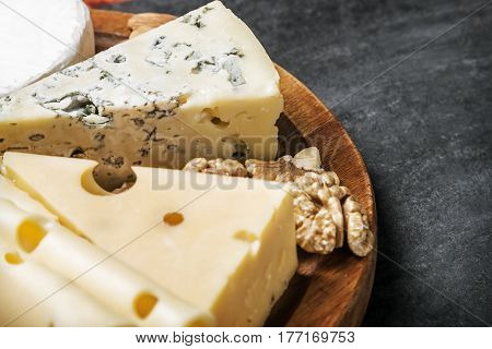 Assorted fresh cheese and nuts on a wooden table