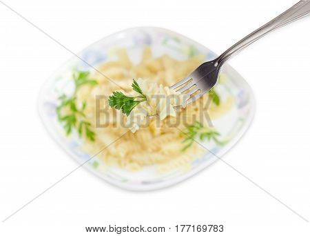Several cooked spiral pasta and parsley twig on the fork closeup on a blurred background of dish with the same pasta on a light background