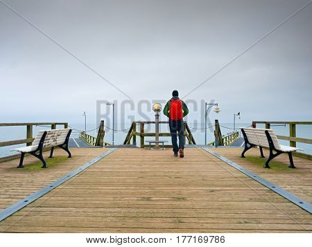 Tourist Walk In Autumn Mist On Wooden Pier Above Sea. Rainy Day