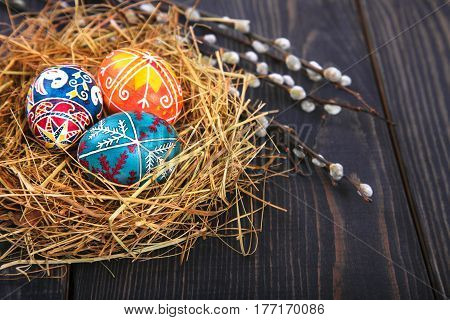 Easter eggs in a basket with willow twigs on a wooden table. The concept of the Easter holidays and folk art.