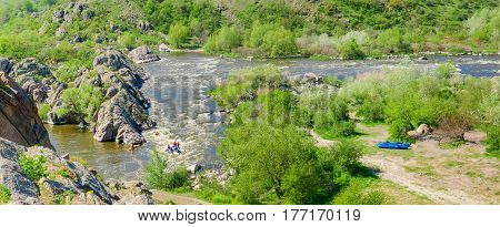 Panorama of the river section with rapids and rock outcrops and trees on its banks on a spring day