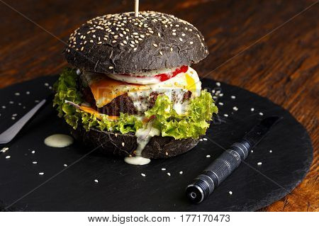 black burger with beef cutlet with vegetables sesame oil shale on the board on a dark background