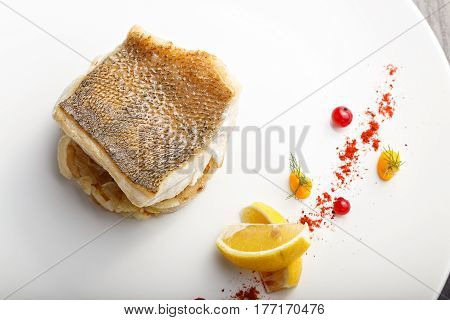 cooked fish fillet of pike-perch on a bed of onion served with a lemon and red currant