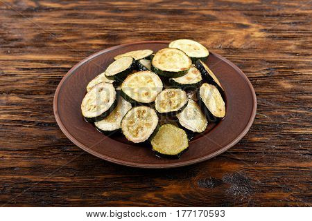 Fried zucchini in a clay plate on a wooden table.