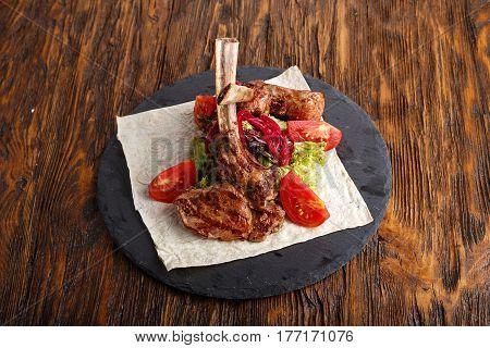 ribeye steak on the bone tomahawk served with tomatoes and iceberg lettuce on pita on slate board.