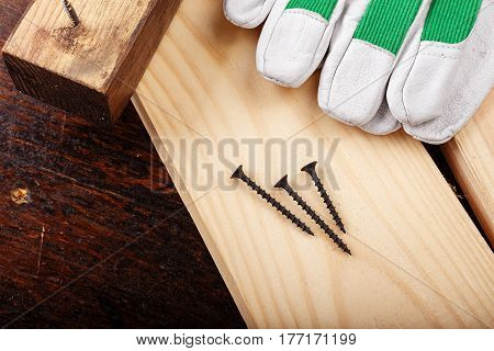 Nails on a log next to carpenter's working gloves horizontal photo