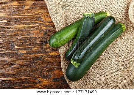 fresh zucchini on a natural brown wooden background. Zucchini are vertical.