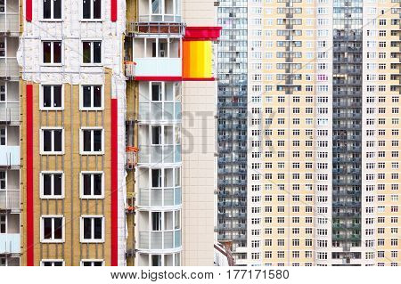 Exterior house wall heat insulation with mineral wool, building residential building on town background