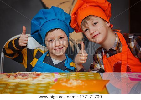 Happy two brothers in the kitchen. Children preparing pizza.