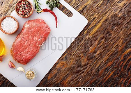raw steak on a kitchen board with spices - salt pepper herbs garlic and olive oil top view