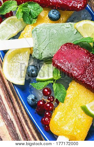 Fruit ice cream on a stick of red currant and citrus on a wooden table.