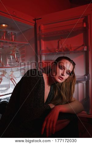Side view of calm woman in dress which sitting near the fridge and looking at camera being indoor with red lighting. Conceptual picture