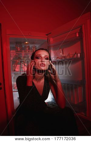 Vertical image of woman in dress which sitting near fridge with hands near the head and looking at camera being indoor with red lighting. Conceptual picture