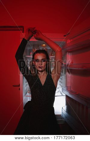 Vertical image of young woman posing near the fridge indoor and looking at camera. Conceptual image