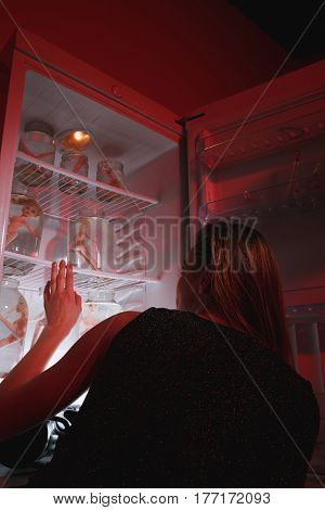 Back view of woman in dress which looking at fridge with dolls in jars. Vertical image. Conceptual photo