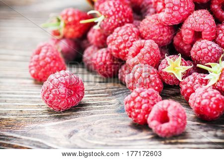 Raspberry fresh on a wooden table. Vignetting as an artistic effect