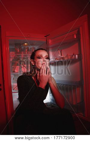 Vertical image of young woman sitting near the fridge and looking at camera indoor with red lighting. Conceptual picture