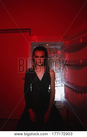 Vertical image of calm woman sitting near the fridge indoor and looking at camera. Concept image