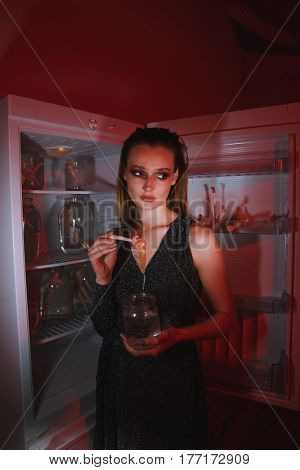 Side view of calm woman in dress which holding doll and jar while standing near the fridge. Vertical image. Conceptual photo