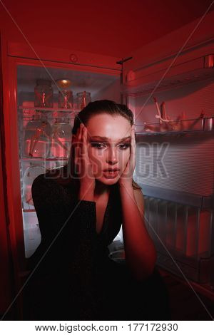 Vertical image of unusual woman in dress which sitting near the fridge and looking at camera bieng indoor with red lighting. Conceptual picture