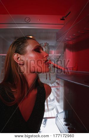 Side view of woman in dress which licking doll which lying on door of firdge. Vertical image. Conceptual picture