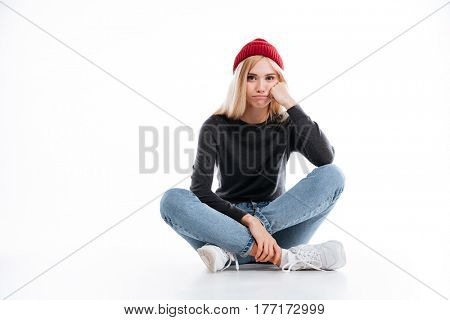 Bored female hipster sitting on the floor while looking at camera over white background