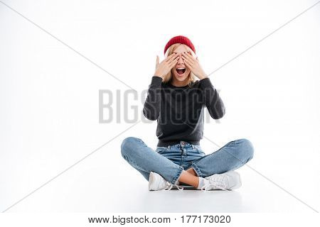 Happy female hipster covering her eyes while sitting on the floor in studio with open open mouth over white background