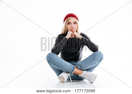 Young female hipster sitting on the floor in studio and looking at camera over white background