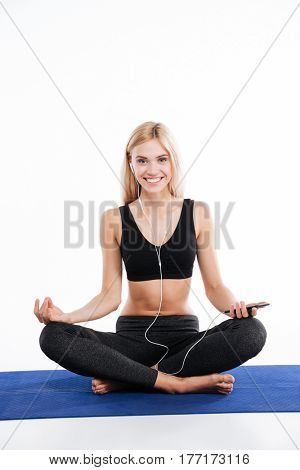 Image of cheerful fitness woman sitting make yoga exercises and posing isolated over white background. Listening music with earphones.