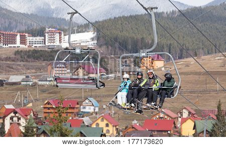 Bukovel Ukraine March 15 2017: Skiers in ski suits and with skis on the ski lift.