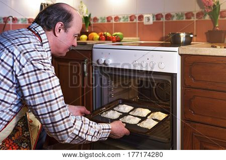 An Elderly Man In An Apron Prepares Pies At Home. A Hospitable Host Prepares Sweets For Guests